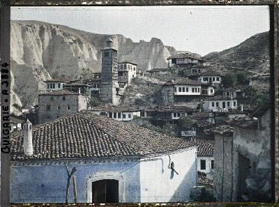 Maisons dont une, au premier plan, peinte en bleu, et tour de bois avec à l\'arrière-plan les falaises de grès. Melnik, Bulgarie, 18 septembre 1913.